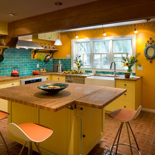 Photo of a rural u-shaped enclosed kitchen in Denver with a belfast sink, yellow cabinets, wood worktops, metro tiled splashback and stainless steel appliances.