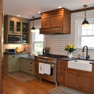 ニューヨークの小さいカントリー風おしゃれなキッチン (エプロンフロントシンク、シェーカースタイル扉のキャビネット、中間色木目調キャビネット、クオーツストーンカウンター、白いキッチンパネル、サブウェイタイルのキッチンパネル、シルバーの調理設備、淡色無垢フローリング、グレーのキッチンカウンター、茶色い床) の写真