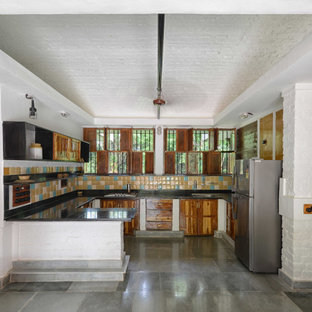 Design ideas for a large country u-shaped kitchen in Mumbai with a farmhouse sink, medium wood cabinets, granite benchtops, multi-coloured splashback, ceramic splashback, marble floors, multi-coloured floor, black benchtop and vaulted.