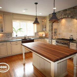 Geschlossene, Große Klassische Küche in U-Form mit Landhausspüle, profilierten Schrankfronten, gelben Schränken, Speckstein-Arbeitsplatte, Küchenrückwand in Beige, Rückwand aus Steinfliesen, Küchengeräten aus Edelstahl und braunem Holzboden in Newark