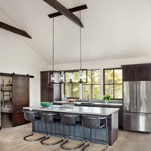 他の地域のラスティックスタイルのおしゃれなアイランドキッチン (エプロンフロントシンク、シェーカースタイル扉のキャビネット、濃色木目調キャビネット、ガラスまたは窓のキッチンパネル、シルバーの調理設備、淡色無垢フローリング、ベージュの床、コンクリートカウンター) の写真