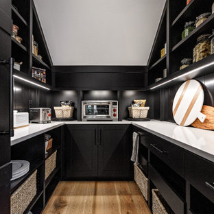 Design ideas for a country u-shaped kitchen pantry in Portland with open cabinets, black cabinets, black splashback, light hardwood floors and white benchtop.