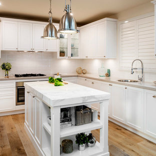Beach style kitchen pictures - Inspiration for a beach style u-shaped light wood floor kitchen remodel in Gold Coast - Tweed with a single-bowl sink, recessed-panel cabinets, white cabinets, white backsplash, stainless steel appliances and an island