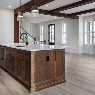 Mid-sized country l-shaped kitchen pantry in Edmonton with an undermount sink, shaker cabinets, medium wood cabinets, quartz benchtops, white splashback, ceramic splashback, stainless steel appliances, vinyl floors, with island, beige floor and white benchtop.