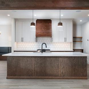 Bild på ett mellanstort lantligt vit vitt kök, med en undermonterad diskho, skåp i shakerstil, skåp i mellenmörkt trä, bänkskiva i kvarts, vitt stänkskydd, stänkskydd i keramik, rostfria vitvaror, vinylgolv, en köksö och beiget golv
