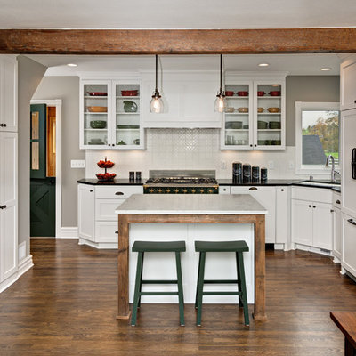 Inspiration for a mid-sized country l-shaped dark wood floor open concept kitchen remodel in Minneapolis with an undermount sink, shaker cabinets, white cabinets, white backsplash, an island, soapstone countertops, ceramic backsplash and paneled appliances