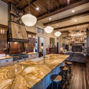 Idéer för ett stort rustikt kök med öppen planlösning, med en rustik diskho, luckor med upphöjd panel, skåp i mörkt trä, bänkskiva i onyx, rostfria vitvaror, mörkt trägolv och en köksö