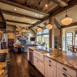 Photo of a mid-sized country galley open plan kitchen in Other with a farmhouse sink, raised-panel cabinets, white cabinets, onyx benchtops, stainless steel appliances, medium hardwood floors and with island.