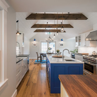 Mid-sized farmhouse eat-in kitchen ideas - Eat-in kitchen - mid-sized farmhouse galley medium tone wood floor eat-in kitchen idea in Boston with a farmhouse sink, flat-panel cabinets, blue cabinets, granite countertops, white backsplash, porcelain backsplash, stainless steel appliances and two islands