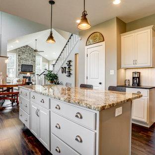 Landhaus Wohnküche in L-Form mit Landhausspüle, weißen Schränken, Granit-Arbeitsplatte, Küchenrückwand in Weiß, Rückwand aus Holzdielen, Küchengeräten aus Edelstahl, Vinylboden, Kücheninsel, braunem Boden und schwarzer Arbeitsplatte