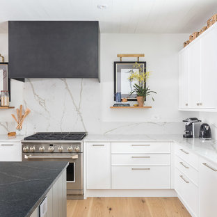 Large transitional l-shaped light wood floor eat-in kitchen photo in Ottawa with an undermount sink, shaker cabinets, white cabinets, quartz countertops, white backsplash, porcelain backsplash, stainless steel appliances and an island