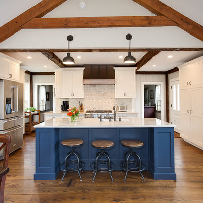 Example of a large country medium tone wood floor and brown floor eat-in kitchen design in Providence with white cabinets, quartzite countertops, white backsplash, brick backsplash, stainless steel appliances, an island and shaker cabinets