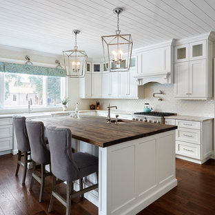 Farmhouse eat-in kitchen remodeling - Inspiration for a farmhouse l-shaped medium tone wood floor and brown floor eat-in kitchen remodel in Toronto with recessed-panel cabinets, white cabinets, wood countertops, ceramic backsplash, stainless steel appliances, an island, an undermount sink, white backsplash and brown countertops