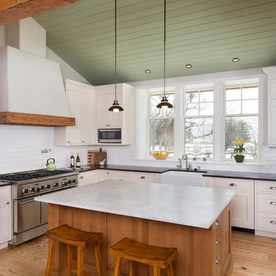 Eat-in kitchen - large cottage l-shaped medium tone wood floor and brown floor eat-in kitchen idea in Denver with a farmhouse sink, shaker cabinets, white cabinets, white backsplash, an island, quartz countertops, subway tile backsplash, paneled appliances and black countertops
