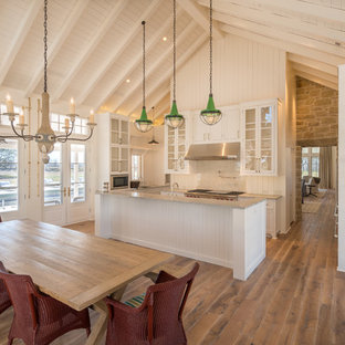 This is an example of a rural u-shaped kitchen/diner in Austin with glass-front cabinets, medium hardwood flooring, an island, white cabinets, white splashback, stainless steel appliances, brown floors and grey worktops.