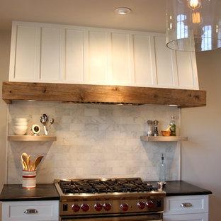 ニューヨークの中サイズのエクレクティックスタイルのおしゃれなアイランドキッチン (エプロンフロントシンク、シルバーの調理設備、無垢フローリング、シェーカースタイル扉のキャビネット、白いキャビネット、ソープストーンカウンター、白いキッチンパネル、大理石のキッチンパネル、茶色い床) の写真