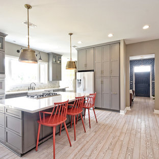 Beach style kitchen appliance - Example of a coastal l-shaped light wood floor and beige floor kitchen design in Austin with a farmhouse sink, shaker cabinets, gray cabinets, white appliances, an island and white countertops