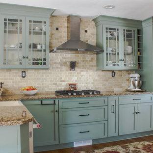 デトロイトの広いカントリー風おしゃれなキッチン (エプロンフロントシンク、シェーカースタイル扉のキャビネット、緑のキャビネット、クオーツストーンカウンター、ベージュキッチンパネル、トラバーチンのキッチンパネル、シルバーの調理設備、無垢フローリング、茶色い床、茶色いキッチンカウンター) の写真