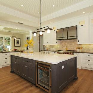 ロサンゼルスの大きいカントリー風おしゃれなキッチン (エプロンフロントシンク、シェーカースタイル扉のキャビネット、白いキャビネット、人工大理石カウンター、茶色いキッチンパネル、テラコッタタイルのキッチンパネル、シルバーの調理設備の、無垢フローリング) の写真