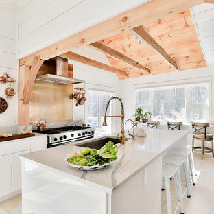 Large farmhouse open concept kitchen photos - Inspiration for a large farmhouse galley light wood floor and beige floor open concept kitchen remodel in New York with an undermount sink, flat-panel cabinets, white cabinets, quartz countertops, metallic backsplash, an island, gray countertops, metal backsplash and