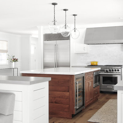 Example of a mid-sized transitional l-shaped medium tone wood floor and brown floor open concept kitchen design in San Francisco with an undermount sink, shaker cabinets, white cabinets, marble countertops, white backsplash, marble backsplash, stainless steel appliances, two islands and white countertops
