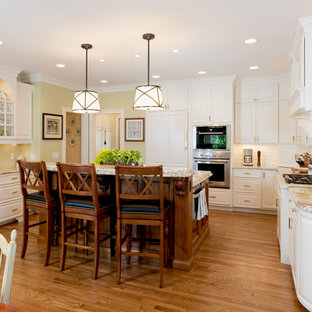 Farmhouse eat-in kitchen inspiration - Example of a cottage eat-in kitchen design in Cincinnati with raised-panel cabinets, white cabinets, white backsplash and stainless steel appliances