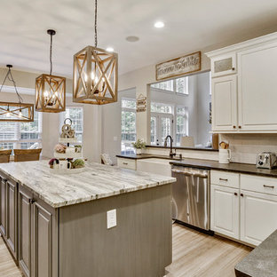 Photo of a mid-sized country u-shaped eat-in kitchen in DC Metro with a farmhouse sink, raised-panel cabinets, beige cabinets, granite benchtops, white splashback, ceramic splashback, stainless steel appliances, bamboo floors, with island, grey floor and grey benchtop.