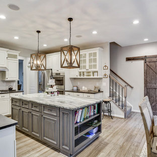 This is an example of a mid-sized country u-shaped eat-in kitchen in DC Metro with a farmhouse sink, raised-panel cabinets, beige cabinets, granite benchtops, white splashback, ceramic splashback, stainless steel appliances, bamboo floors, with island, grey floor and grey benchtop.