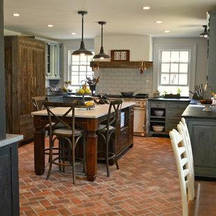 フィラデルフィアの広いカントリー風おしゃれなキッチン (エプロンフロントシンク、レイズドパネル扉のキャビネット、グレーのキャビネット、大理石カウンター、グレーのキッチンパネル、サブウェイタイルのキッチンパネル、白い調理設備、レンガの床、赤い床) の写真