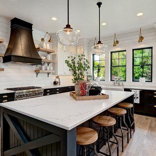 ロサンゼルスのL型カントリー風 キッチンの画像 (クオーツストーンカウンター、エプロンフロントシンク、シェーカースタイル扉のキャビネット、黒いキャビネット、シルバーの調理設備、無垢フローリング、アイランドキッチン、茶色い床)