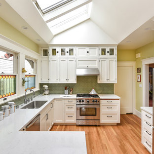 Farmhouse u-shaped kitchen in Los Angeles with engineered stone countertops, a submerged sink, shaker cabinets, white cabinets, green splashback, stainless steel appliances, medium hardwood flooring and a breakfast bar.