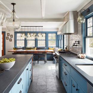 На фото: линейная кухня среднего размера в стиле кантри с обеденным столом, одинарной раковиной, синими фасадами, столешницей из известняка, белым фартуком, фартуком из плитки кабанчик, техникой из нержавеющей стали, полом из сланца, островом и серым полом с