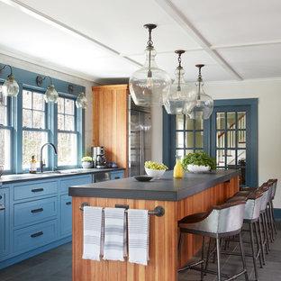 ボストンの中サイズのカントリー風おしゃれなキッチン (シングルシンク、落し込みパネル扉のキャビネット、青いキャビネット、ライムストーンカウンター、サブウェイタイルのキッチンパネル、シルバーの調理設備の、スレートの床、グレーの床、白いキッチンパネル) の写真