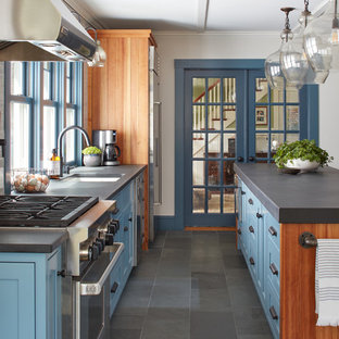 Inspiration for a mid-sized country single-wall eat-in kitchen in Boston with a single-bowl sink, recessed-panel cabinets, blue cabinets, limestone benchtops, blue splashback, subway tile splashback, stainless steel appliances, slate floors, with island and grey floor.