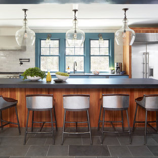 Design ideas for a mid-sized country single-wall eat-in kitchen in Boston with a single-bowl sink, recessed-panel cabinets, blue cabinets, limestone benchtops, subway tile splashback, stainless steel appliances, slate floors, with island, grey floor and white splashback.