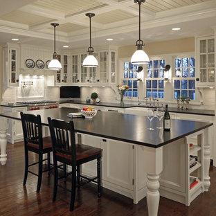 Idéer för att renovera ett lantligt kök, med luckor med glaspanel, vitt stänkskydd, stänkskydd i tunnelbanekakel, integrerade vitvaror, vita skåp och granitbänkskiva