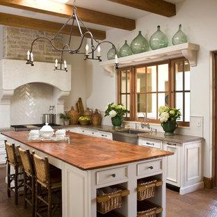 Mediterrane Küche in L-Form mit Landhausspüle, Schrankfronten mit vertiefter Füllung, weißen Schränken, Küchenrückwand in Weiß, Küchengeräten aus Edelstahl, Kücheninsel und Rückwand aus Keramikfliesen in Phoenix