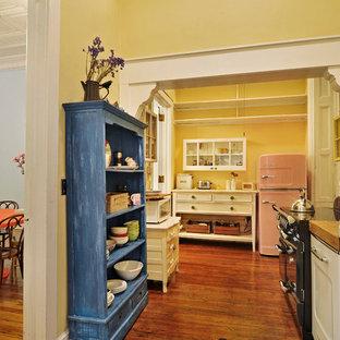 ニューヨークのカントリー風おしゃれなキッチン (オープンシェルフ、ベージュのキャビネット、パネルと同色の調理設備) の写真