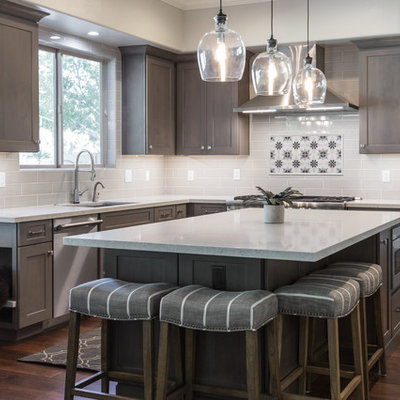 Eat-in kitchen - mid-sized farmhouse u-shaped dark wood floor and brown floor eat-in kitchen idea in Phoenix with an undermount sink, shaker cabinets, dark wood cabinets, solid surface countertops, white backsplash, subway tile backsplash, stainless steel appliances, an island and white countertops