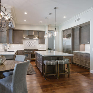 Mid-sized transitional u-shaped dark wood floor and brown floor eat-in kitchen photo in Phoenix with an undermount sink, shaker cabinets, dark wood cabinets, white backsplash, stainless steel appliances, an island, white countertops, solid surface countertops and subway tile backsplash
