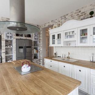 ロサンゼルスのカントリー風おしゃれなキッチン (ドロップインシンク、レイズドパネル扉のキャビネット、白いキャビネット、白いキッチンパネル、シルバーの調理設備の) の写真