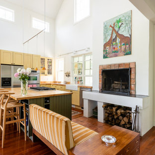 Farmhouse kitchen ideas - Kitchen - farmhouse l-shaped medium tone wood floor, brown floor and vaulted ceiling kitchen idea in Boston with a farmhouse sink, shaker cabinets, yellow cabinets, wood countertops, stainless steel appliances and an island