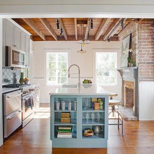 アトランタの小さいカントリー風おしゃれなキッチン (エプロンフロントシンク、シェーカースタイル扉のキャビネット、グレーのキャビネット、クオーツストーンカウンター、青いキッチンパネル、テラコッタタイルのキッチンパネル、シルバーの調理設備の、無垢フローリング、茶色い床) の写真