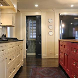 ニューヨークの大きいカントリー風おしゃれなキッチン (アンダーカウンターシンク、フラットパネル扉のキャビネット、赤いキャビネット、木材カウンター、マルチカラーのキッチンパネル、ガラス板のキッチンパネル、黒い調理設備、濃色無垢フローリング) の写真