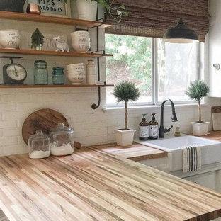 コロンバスの小さいカントリー風おしゃれな独立型キッチン (エプロンフロントシンク、フラットパネル扉のキャビネット、白いキャビネット、木材カウンター、白いキッチンパネル、レンガのキッチンパネル、シルバーの調理設備、濃色無垢フローリング、アイランドなし、茶色い床、茶色いキッチンカウンター) の写真