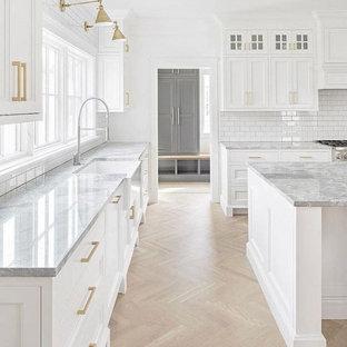 Стильный дизайн: большая угловая кухня-гостиная в стиле кантри с раковиной в стиле кантри, белыми фасадами, мраморной столешницей, белым фартуком, фартуком из плитки кабанчик, техникой из нержавеющей стали, светлым паркетным полом, коричневым полом, белой столешницей, островом и фасадами в стиле шейкер - последний тренд