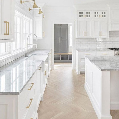 Inspiration for a large cottage l-shaped light wood floor and brown floor open concept kitchen remodel in Columbus with a farmhouse sink, white cabinets, marble countertops, white backsplash, subway tile backsplash, stainless steel appliances, white countertops, an island and shaker cabinets