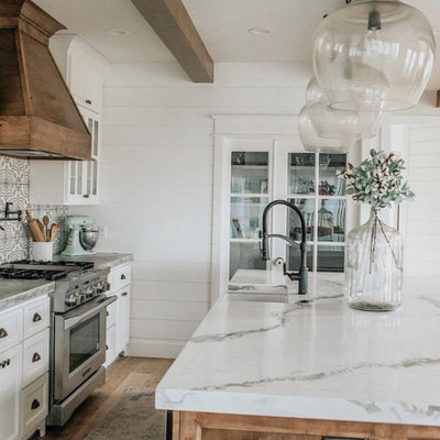 Inspiration for a large country galley light wood floor and brown floor open concept kitchen remodel in Columbus with a farmhouse sink, shaker cabinets, white cabinets, quartzite countertops, multicolored backsplash, mosaic tile backsplash, stainless steel appliances, an island and white countertops