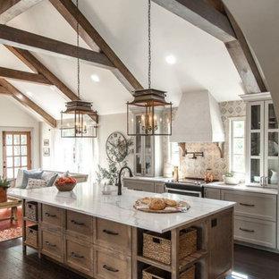 コロンバスの広いカントリー風おしゃれなキッチン (エプロンフロントシンク、シェーカースタイル扉のキャビネット、中間色木目調キャビネット、大理石カウンター、マルチカラーのキッチンパネル、シルバーの調理設備、濃色無垢フローリング、茶色い床、白いキッチンカウンター) の写真