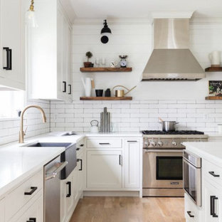 Large farmhouse open concept kitchen ideas - Large farmhouse single-wall light wood floor and brown floor open concept kitchen photo in Columbus with a farmhouse sink, shaker cabinets, white cabinets, quartzite countertops, white backsplash, subway tile backsplash, stainless steel appliances, an island and white countertops